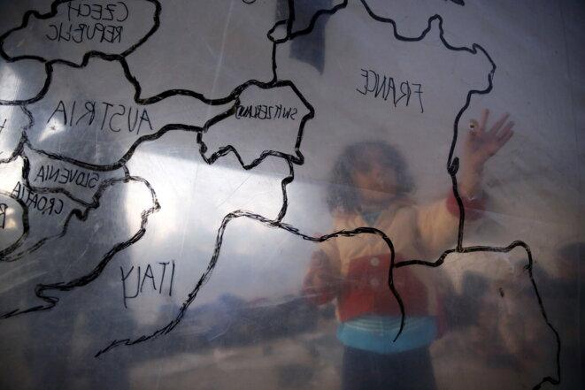 Un enfant réfugié devant une carte de l'Europe, dans un campement près d'un centre d'enregistrement sur l'île de Lesbos, le 18 novembre 2015 © Reuters