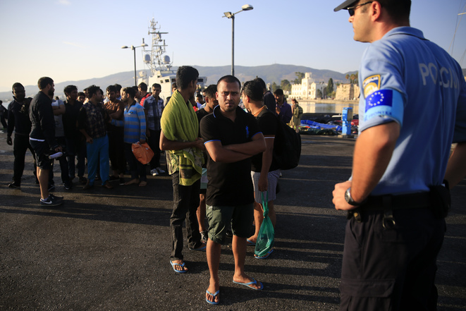 Des migrants réceptionnés par un agent de Frontex à leur arrivée à Kos en Grèce, le 14 août 2015. © Reuters