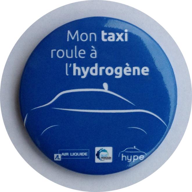 Badge distribué le 7 décembre 2015 sur le Cours Albert 1er © hype (www.taxioo.com)