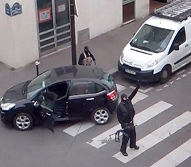 Chérif et Saïd Kouachi, sortant des locaux de Charlie Hebdo où ils ont assassiné onze personnes. Dans quelques instants, ils vont s'en prendre aux policiers arrivant dans la rue. © Reuters