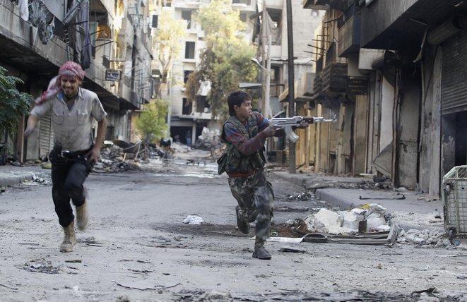 Un enfant de 13 ans, membre de l'Armée syrienne libre, dans les rues d'Alep © Reuters