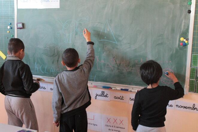Mohamed (à droite) et deux autres élèves dans une classe installée dans un préfabriqué à l'école Saint-Louis Consolat © Margaïd Quioc