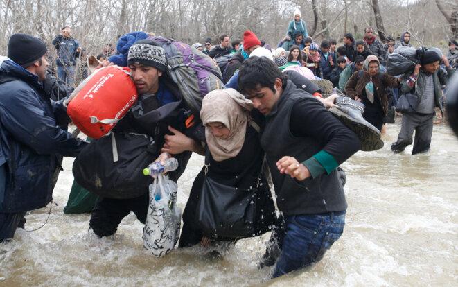 Lundi 14 mars 2016, des centaines de migrants traversent une rivière en crue pour rejoindre la Macédoine, avant de se faire refouler © Reuters