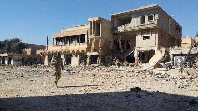 Un soldado leal al gobierno de Tobruk camina frente a las ruinas en Bengasi. © Reuters