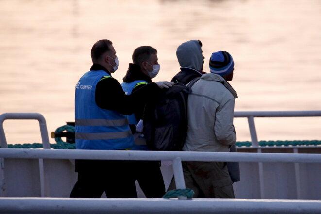 Frontex embarque des migrants au port de Mytilène (Lesbos) pour les renvoyer en Turquie, au petit matin du lundi 4 avril 2016 © Reuters / Yorgos Moutafis