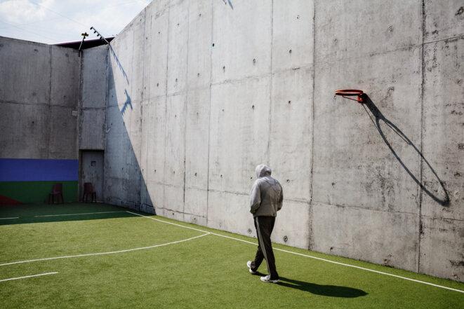Un détenu parcourt un terrain de sport dans une prison © Grégoire Korganow / CGLPL