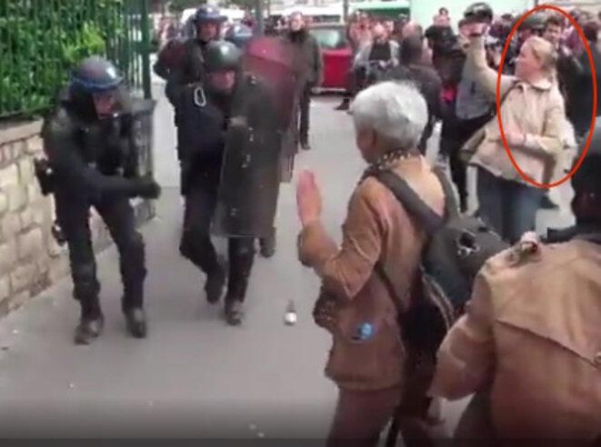Le policier lance la grenade, sous les yeux de Romain D., derrière la jeune femme qui filme la scène. © Capture d'écran de la vidéo réalisée par LDC.