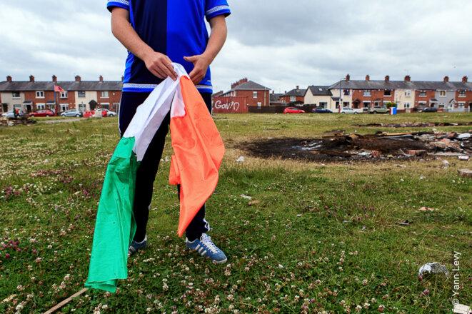 """Un gamin du """"Village"""" s'amuse avec un drapeau républicain, il l'accrochera au sommet du Bonfire pour le bruler avec d'autres  symboles nationalistes ou catholiques. © Yann Levy / Reproduction partielle ou totale strictement interdite"""