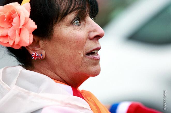 Une femme assiste au défilé des fanfares loyalistes, elle est aux couleurs de l'Union Jack de la tête aux pieds. © Yann Levy / Reproduction partielle ou totale strictement interdite