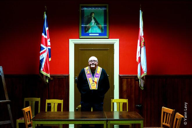 Spencer Beattie pose sous le portrait de la reine d'Angleterre dans la principale salle de réunion de sa loge orangiste. © Yann Levy / Reproduction partielle ou totale strictement interdite