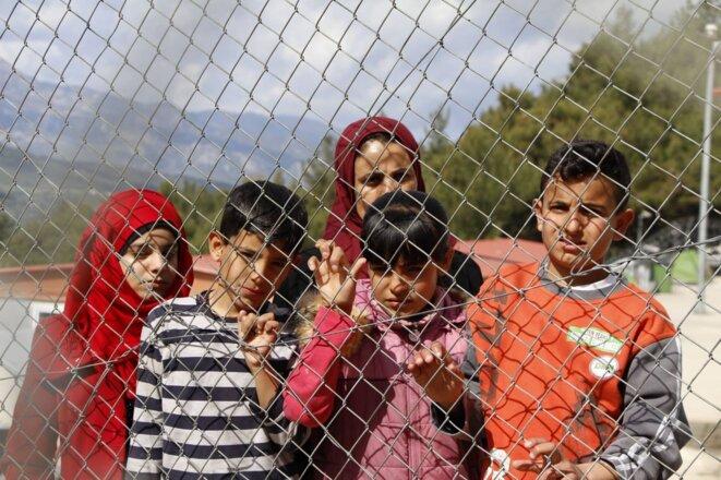 Derrière les barbelés du camp de rétention de l'île grecque de Samos, Khadija, une réfugiée syrienne veuve, et ses enfants. © Mohammad Ghannam pour MSF