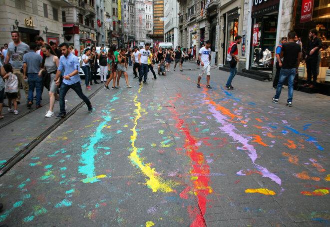 Quelques activistes lesbiennes viennent de déverser des peintures aux couleurs du Rainbow flag, symbole des luttes LGBT, sur les pavés de la célèbre avenue Istiklal. Cet emblème sera pourchassé toute la journée par les policiers en uniforme ou en civil. Istanbul, 26 juin 2016. © Anne-Sophie Zika