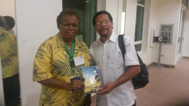 """À droite, le Dr Carlyle G. Corbin ( Îles Vierges), International Advisor on Governance ; À gauche, Attorney J. Roman Bedor, membre de  Rubekul Belau, le Conseil des Chefs de Palau, Conseiller du Président de la République de Palau, auteur de """"Palau - To Independent Nation from the Colonial Outpost"""" présentant son livre au Dr. Carlyle G' Corbin à l'occasion d'une signature à l'université de Guam."""
