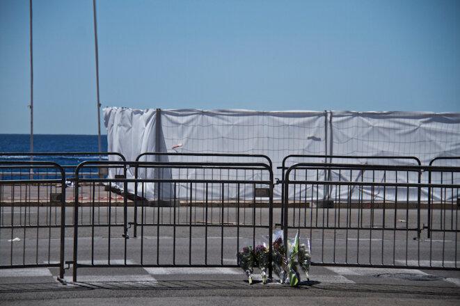 Des barrières avec des fleurs déposées par les Niçois sur la promenade des Anglais. © LG