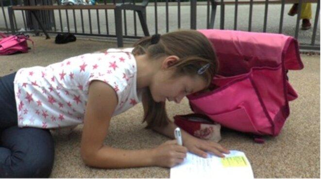 En septembre Olta fait ses devoirs dans le square devant la gare