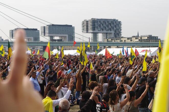 La foule s'est tue, levant la main, doigts en V, signe de victoire, au moment de la commémoration des martyrs tombéEs pour la liberté du Kurdistan.