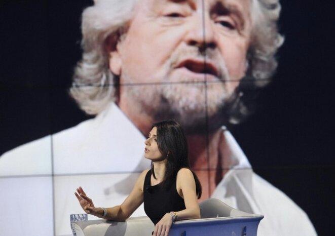 Virginia Raggi lors d'une émission de télévision, avec Beppe Grillo en fond d'écran derrière elle © Capture d'écran L'unita.tv