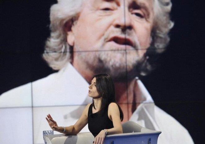 Virginia Raggi durante un programa de televisión, con Beppe Grillo de fondo. © Capture d'écran L'unita.tv