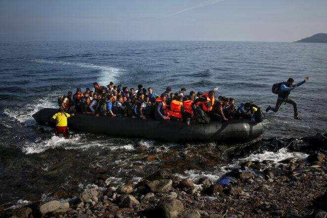 Un exilé afghan saute d'un bateau à son arrivée à Lesbos, en Grèce, le 19 octobre 2015. © Reuters