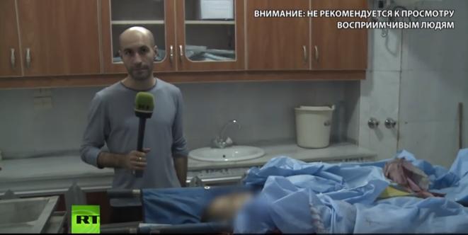 Le correspondant de guerre de Russia Today devant deux petits cadavres d'écoliers, après le pilonnage d'une école dans le quartier chrétien de Souleimaniyé, jeudi 13 octobre. La chaîne a accusé les médias occidentaux de passer sous silence ces morts.