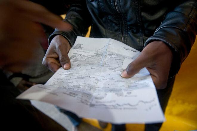 Calais, le 24 octobre 2016. Des cartes de France sont données aux migrants. © Bertrand Gaudillère / Item