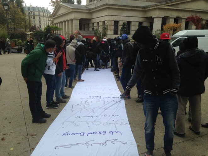 Un activiste a apporté du tissu et des crayons, une banderole s'improvise, à Stalingrad, à Paris, le 26 octobre 2016. © CF