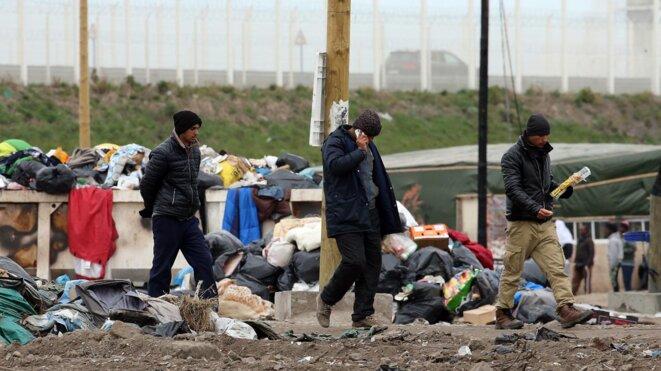 """Des migrants téléphonent depuis la """"jungle"""" de Calais (Nord-Pas-de-Calais), le 5 avril 2016. (MAXPPP)"""