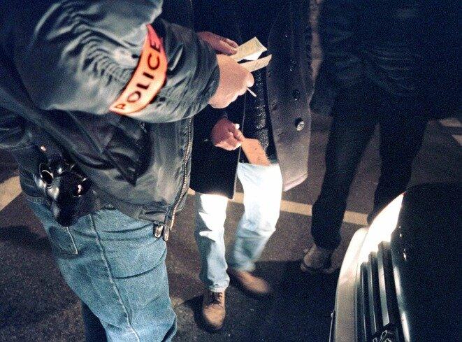 Un policier en civil d'une brigade anticriminalité contrôle l'identité d'une personne durant une patrouille de nuit en 1998 en région parisienne. © REUTERS/Philippe Wojazer