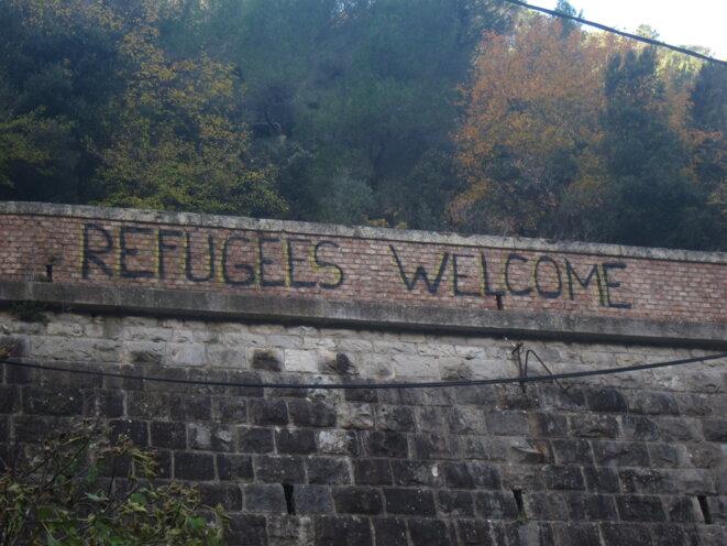 À l'entrée de la vallée de la Roya, juste après la frontière italienne, un tag souhaite la bienvenue aux réfugiés. © LF