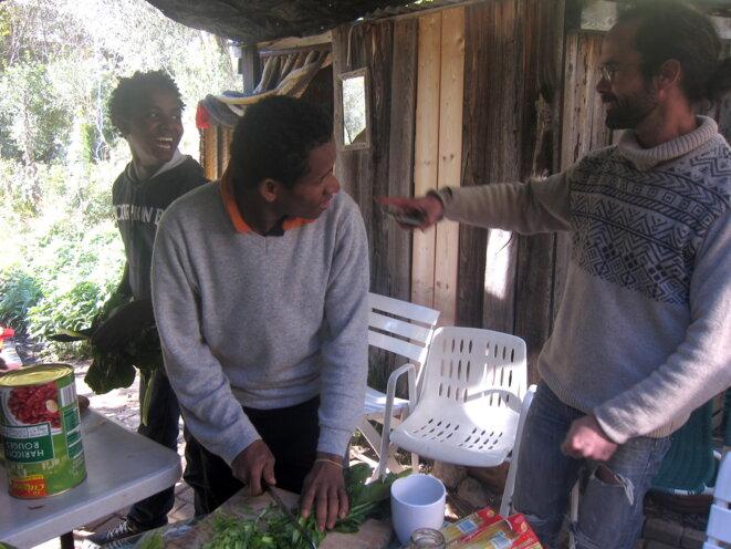 Deux jeunes migrants et Cédric Herrou préparent le repas, à Breil-sur-Roya en novembre 2016. © LF
