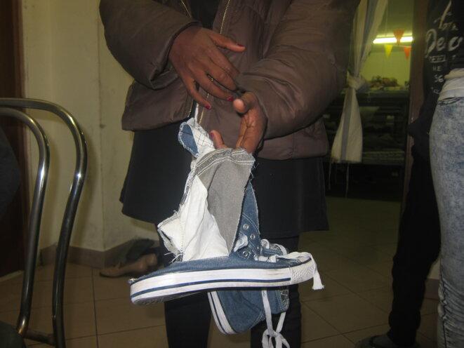 Ruth, une Érythréenne de 22 ans, montre ses chaussures lacérées par la police française, selon elle, pour la décourager. © LF