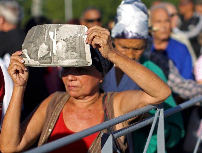 Place de la Révolution, une manifestante se protège avec une pochette montrant Hugo Chavez et Fidel Castro. © Reuters