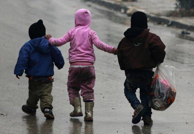 Trois enfants fuient mardi dans les quartiers est d'Alep © Reuters