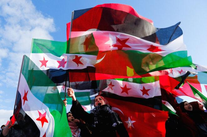 Des drapeaux turcs et de l'armée syrienne libre sont brandis par des manifestants lors du départ d'un convoi d'aide pour la Syrie. © Reuters