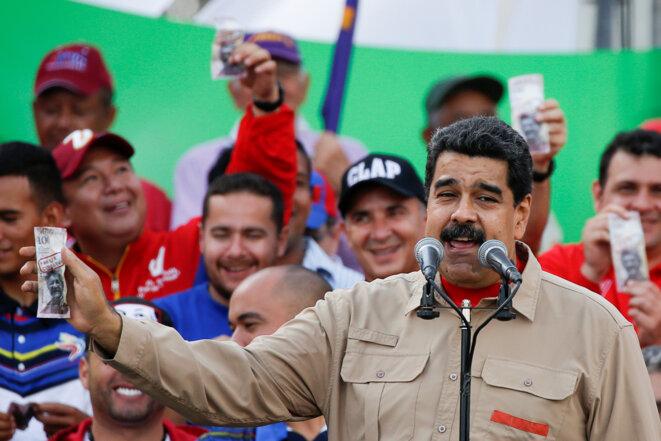 Nicolas Maduro tenant à la main un billet de 100 bolivars, retiré de la circulation. © Reuters