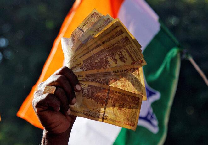 Un homme brandit des billets de 500 roupies lors d'une manifestation organisée par l'opposition, fin novembre 2016. © Reuters
