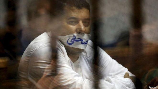 """Un journaliste égyptien emprisonné en 2015 avec le mot """"journaliste"""" écrit sur son bâillon © Reuters"""