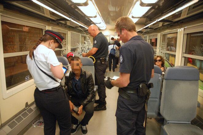 À la gare de Menton-Garavan, le 15 juin 2015, des CRS contrôlent un homme dans le train pour Nice. © LF