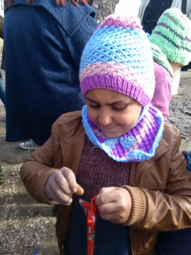Jeune réfugié portant un bonnet tricoté en Grèce par des femmes de l'association  « All you knit is love »