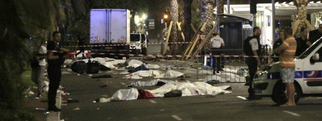 Des corps recouverts d'un drap sur la promenade des Anglais, à Nice (Alpes-Maritimes), après l'attaque d'un chauffeur à bord d'un camion, le 14 juillet 2016. (MAXPPP)