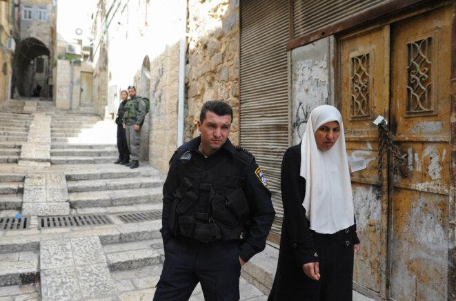 Une Palestinienne passe près d'un policier israélien, venu avec sa patrouille (visible à l'arrière-plan) procéder à l'expulsion d'une famille palestinienne de son logement dans le quartier arabe de la Vieille Ville de Jérusalem © Mehdi Chebil