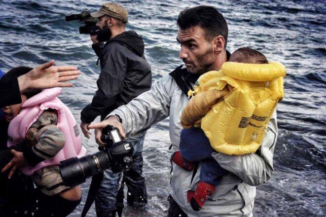 aris-messinis-transporte-un-enfant-sur-le-rivage-a-lesbos