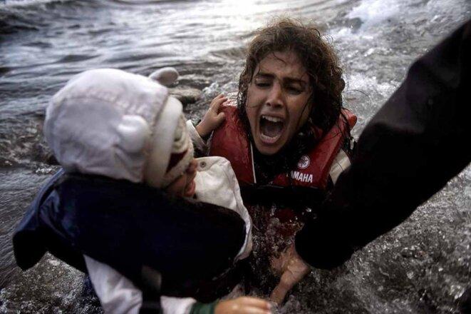 une-femme-tombe-a-l-eau-avec-son-enfant-sur-une-plage-a-lesbos-apres-avoir-traverse-la-mer-egee-octobre-2016-refugies-aris-messinis