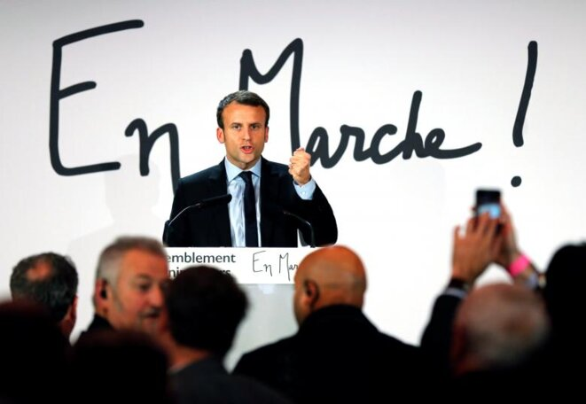 Emmanuel Macron devant le logo d'un mouvement qui porte ses initiales © Reuters