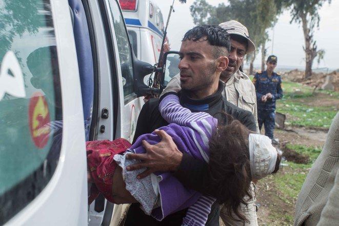 Una joven es transportada, el 15 de marzo, en una ambulancia hasta el aeropuerto de Mosul. De acuerdo con los testigos, la joven perdió a 19 miembros de su familia en un ataque que mató a 26 personas en la zona Mahatta. © Jérémy André