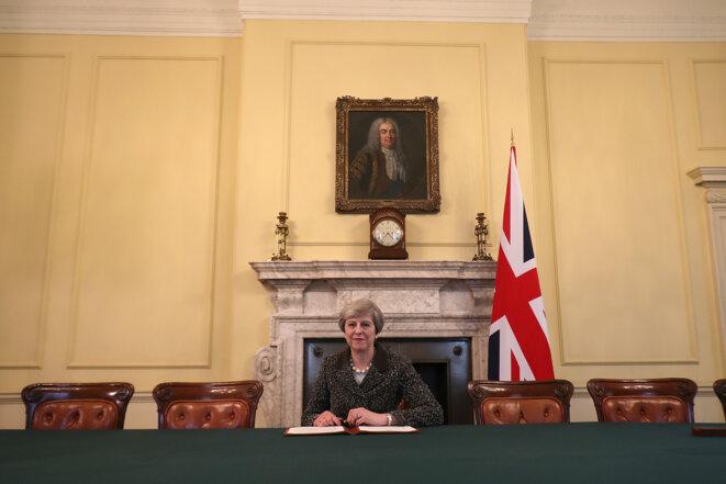 Theresa May, le 28 mars 2017 à Londres, signe la lettre sur le déclenchement de l'article 50, qui doit être remise ce mercredi à Bruxelles. © Reuters / Christopher Furlong.