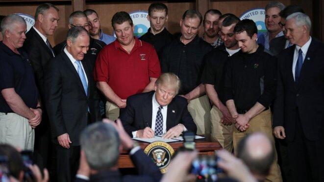 Mardi 28 mars à la Maison Blanche, Donald Trump entouré de mineurs venus de Virginie-Occidentale. © Reuters
