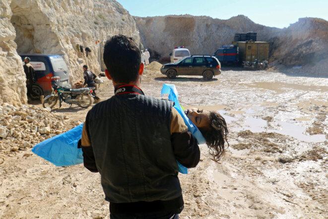 Une enfant victime de l'attaque chimique du 4 avril 2017 à Khan Cheikhoun est transportée par un secouriste. © Ammar Abdullah/Reuters