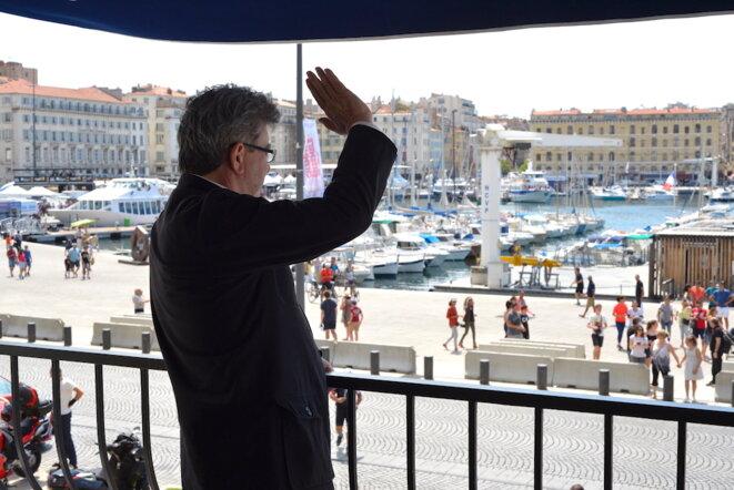 Jean-Luc Mélenchon salue des supporteurs de rugby depuis le balcon d'un restaurant à Marseille, mai 2017. © LF
