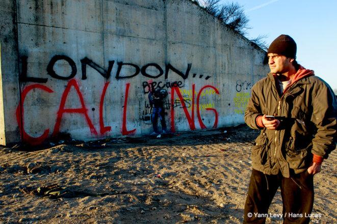 Février 2016, un migrant attends à l'entrée de la Jungle un appel téléphonique. © Yann Levy / Hans Lucas